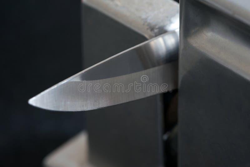 Keukenmes in een scherpend hulpmiddel stock fotografie