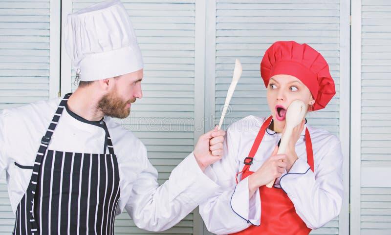 Keukenregels Culinair slagconcept De culinaire vrouw en de gebaarde man tonen concurrenten Who betere kok uiteindelijk stock foto's