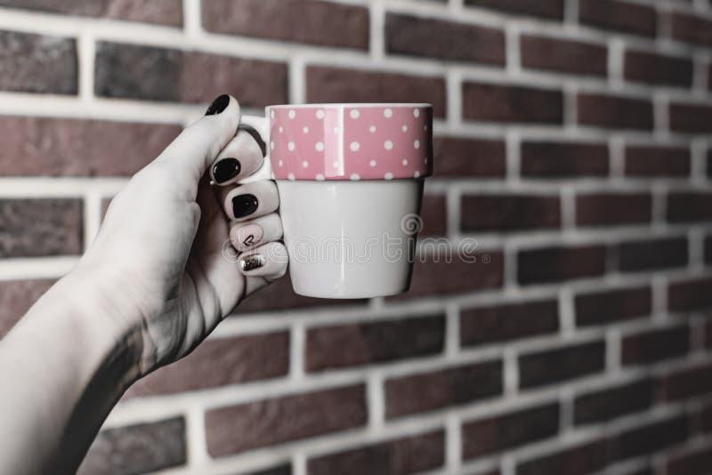 Keukenstilleven, houdt de vrouwelijke hand met mooie manicure een mok roze die wit op een achtergrond van een oude rode baksteen  royalty-vrije stock foto
