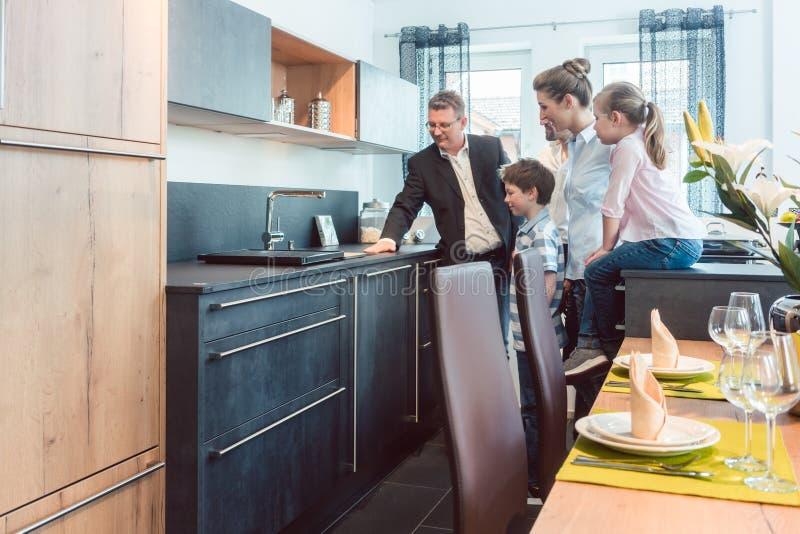 Keukenverkoop met een familie, jonge geitjes, en een de dienstdeskundige stock foto