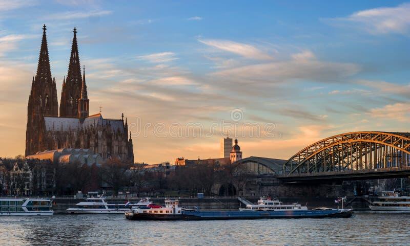 Keulen, Duitsland - Januari 22, 2017: De Kathedraal van Keulen en Hohenzollern-Brug in de stralen van de avondzon Onder stock afbeelding