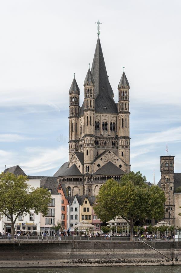 KEULEN, DUITSLAND - SEPTEMBER 11, 2016: Kleurrijke huizen in Beierse stijl en de Romaanse Katholieke kerk ` Brutosankt Martin ` stock fotografie