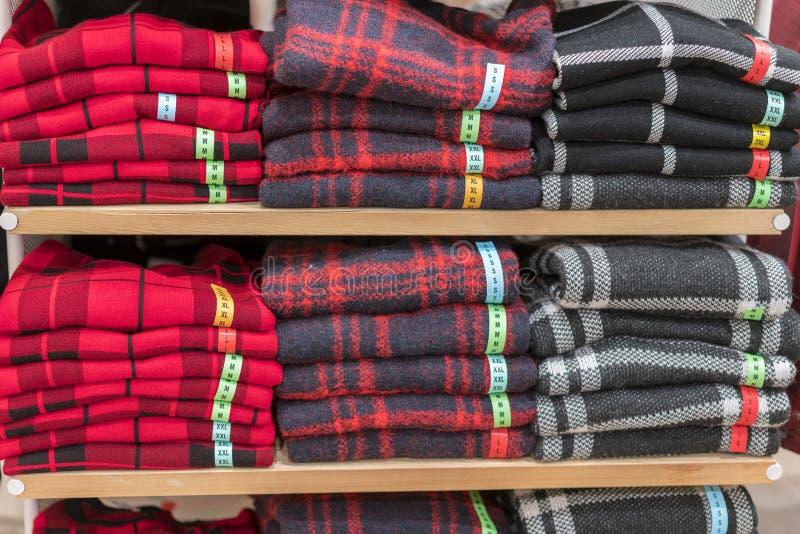 Keurig gevouwen kleren Rek van kleren met warm Houten kabinet met een stapel sweaters Gekleurde kleding Keurige stapels van stock afbeelding