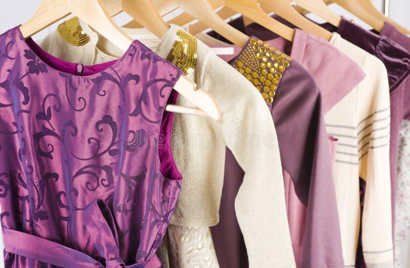 Keurige vrouwelijke kleding met ornament het hangen op een plank stock afbeelding