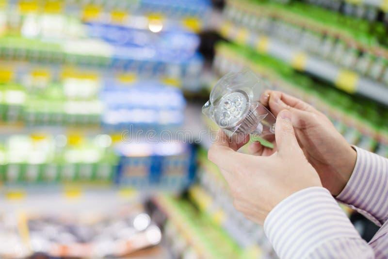 Keus van de energie de efficiënte verlichting: close-up op handen die of van de LEIDENE de lamp diode gloeilamp in het warenhuis  royalty-vrije stock foto's