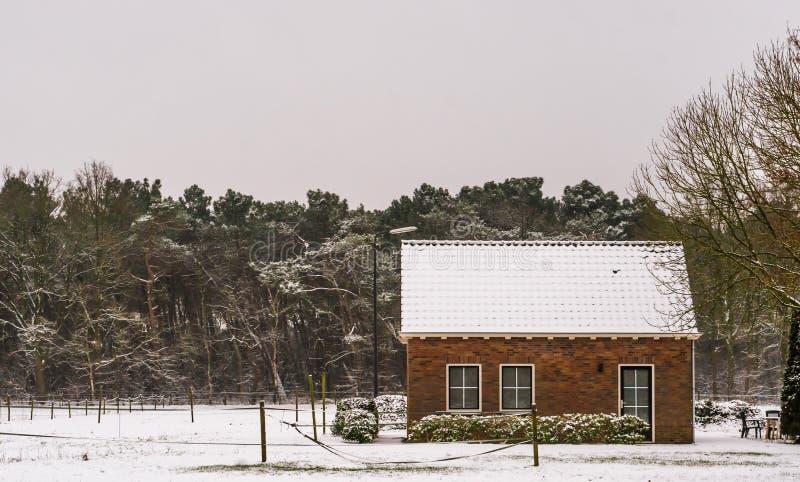 Keuterboertjesplattelandshuisje in een landschap van het de winterlandschap, landbouwbedrijfgebieden en huis in sneeuw wordt beha stock afbeeldingen