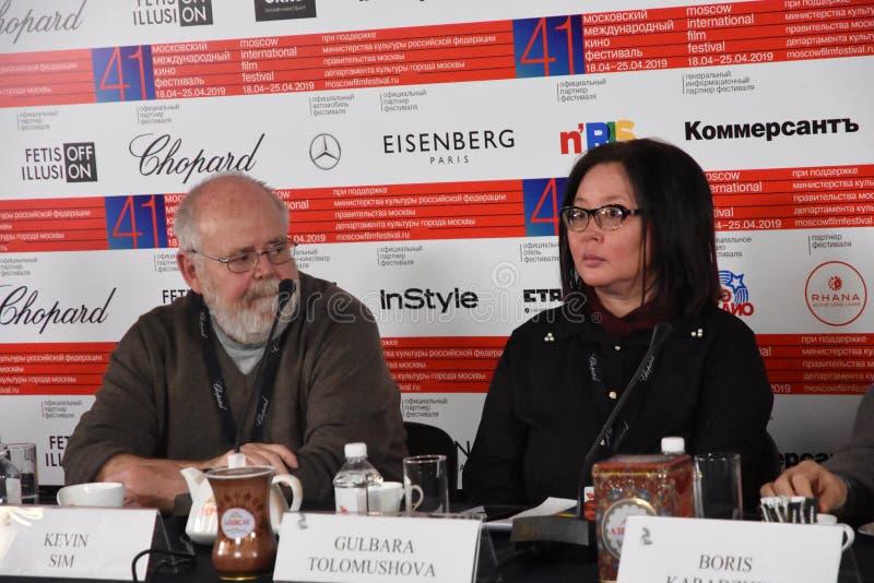 Kevin Sim, Gulbara Tolomushova bij persconferentie royalty-vrije stock afbeeldingen