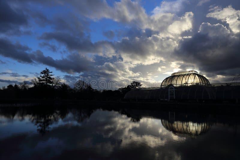 Kew trädgårdar, London, strömförsörjning gömma i handflatan husväxthuset, burken, vintersolnedgång och himmel arkivbilder