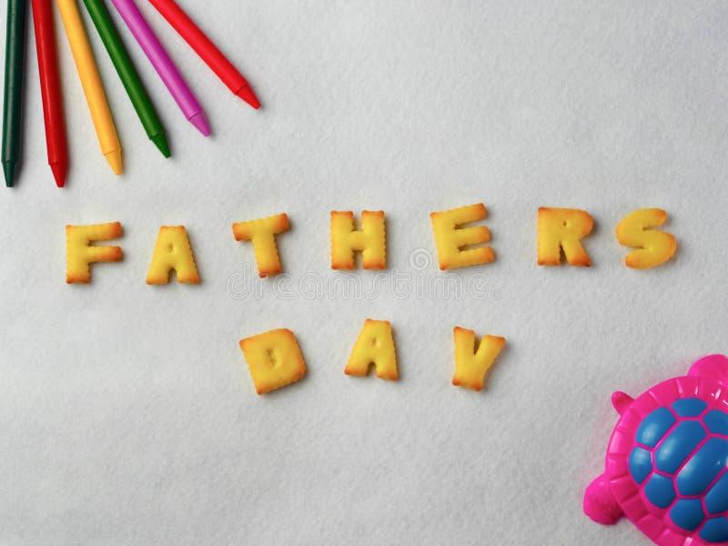 Kex bokstäver, former och färgrika färgpennor, plast- leksaker ordnade på en vit bakgrund för faderns dag royaltyfri foto