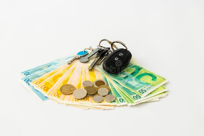 The key binding with the remote control from a car lie on a stack of banknotes and coins of new Israeli shekels - NIS - on a white royalty free stock images