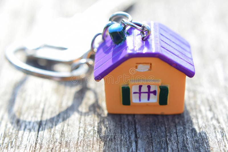 Key chain with colorful house. Shaped pendant on grey weathered wood background with copy space for text. Real estate, buying and moving new home or renting stock photo