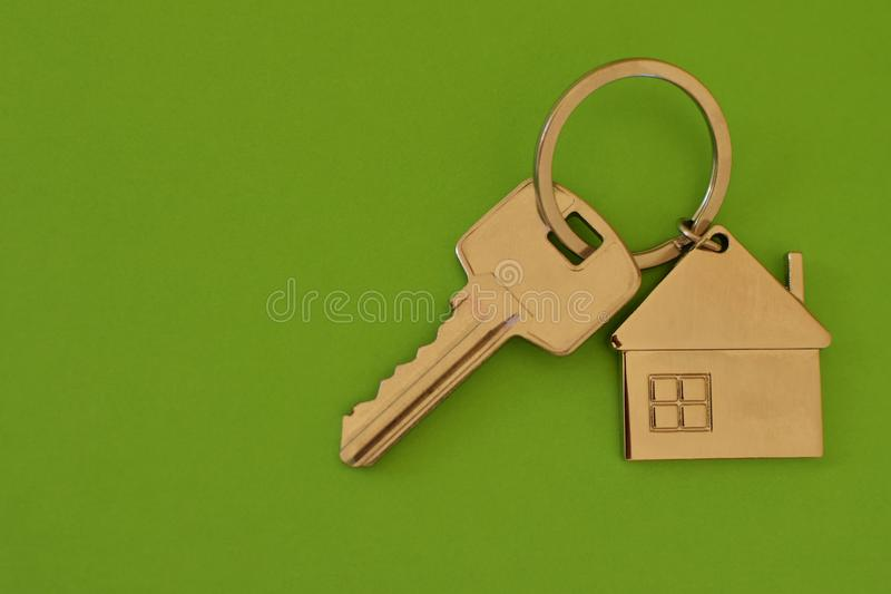 Key chain with house shaped pendant on green. Key chain with silver house shaped pendant on bright green background closeup top view with copy space for text royalty free stock images