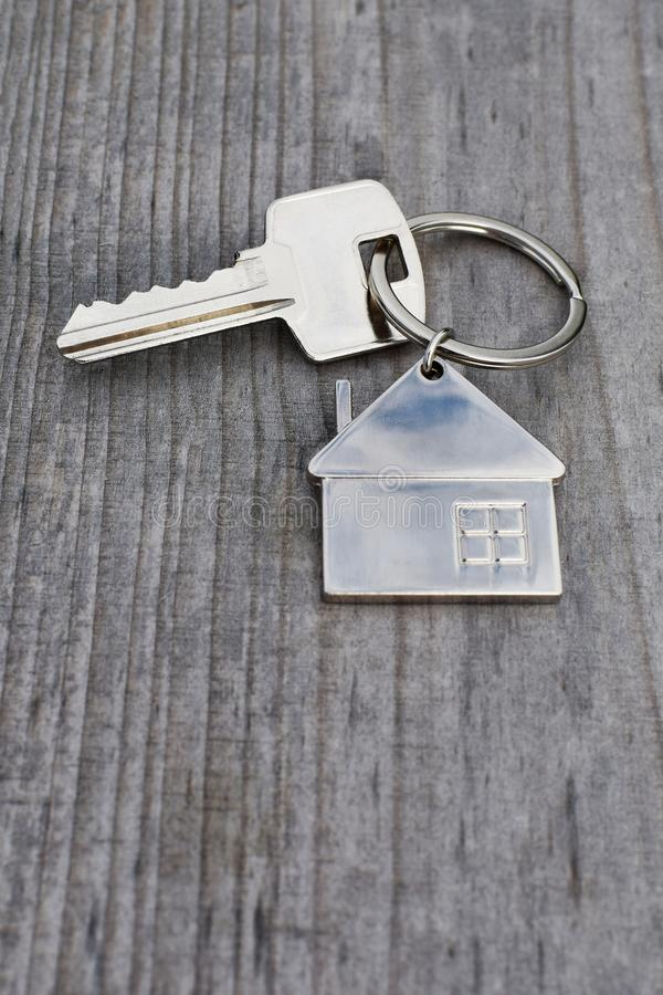 Key chain with house shaped pendant. Key chain with silver house shaped pendant on grey weathered natural wood background with copy space for text. Real estate royalty free stock images