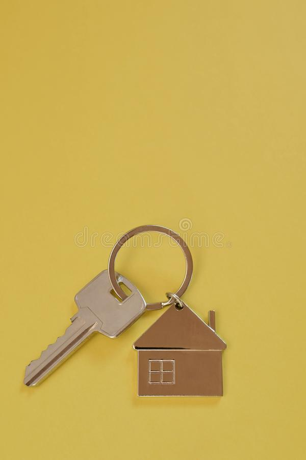 Key chain with house shaped pendant on yellow. Key chain with silver house shaped pendant on yellow background closeup top view with copy space for text. Real royalty free stock photography
