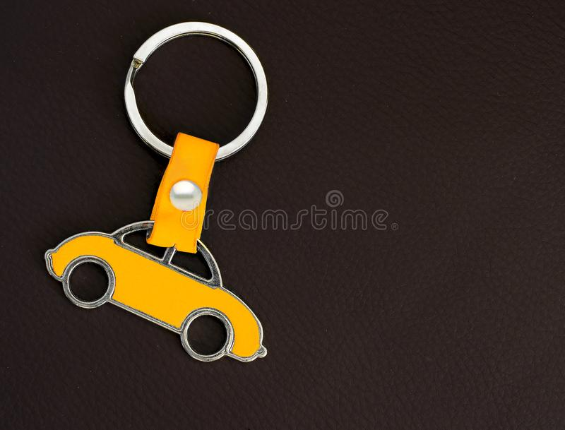 Key chain with a yellow beetle car on dark leather pad as background stock images
