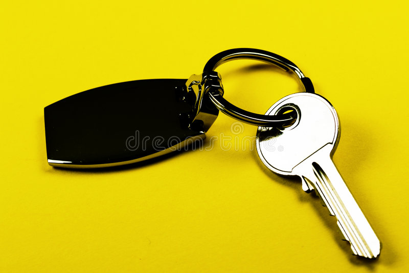 Key close-up. Clear key on keyring - yellow background isolated stock photos