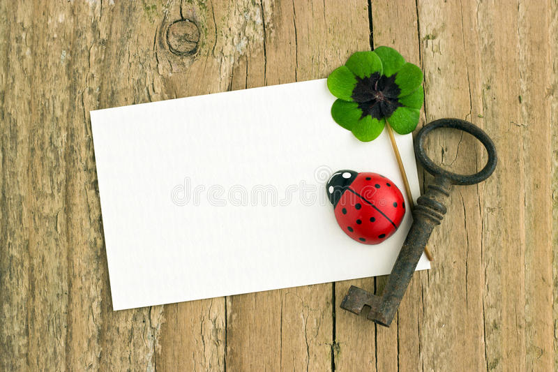 Key and clover. White card with key, ladybugs and clover on board stock photos