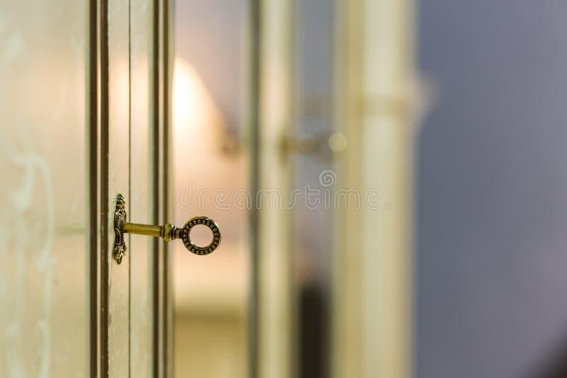 Key in the door lock. Old key in the closet door lock closeup stock photo