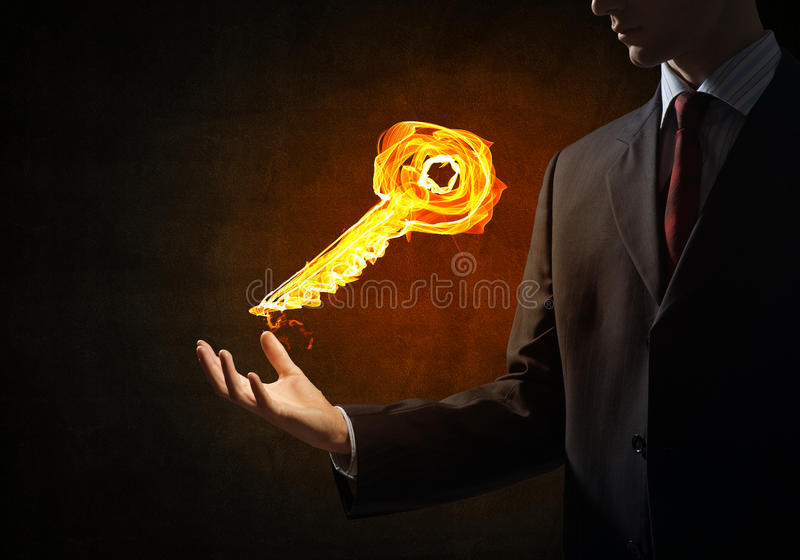 Key fire sign. Close of businessman hand showing fire glowing key symbol stock images