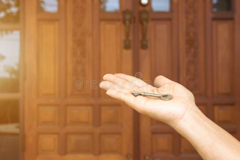 Key on hand of people open the door to inside ,outside door open putting into front door stock images