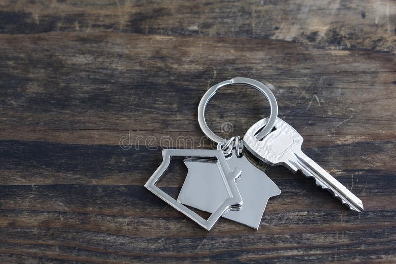 Key and House Pendant on a Rustic Wooden Background stock photos