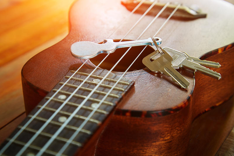 Key with keychain in form of guitar. Put on the ukulele, close up view royalty free stock photo