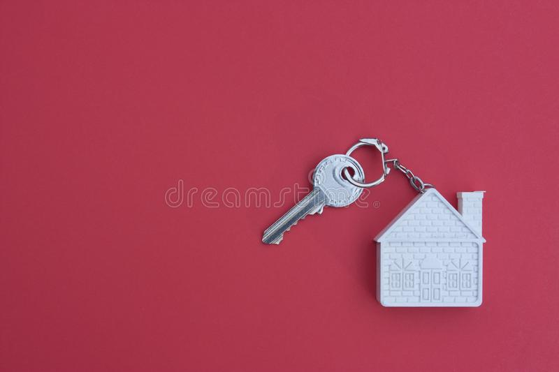 Key with a keychain in the form of a house on a red background. The concept of buying, selling, renting real estate royalty free stock image