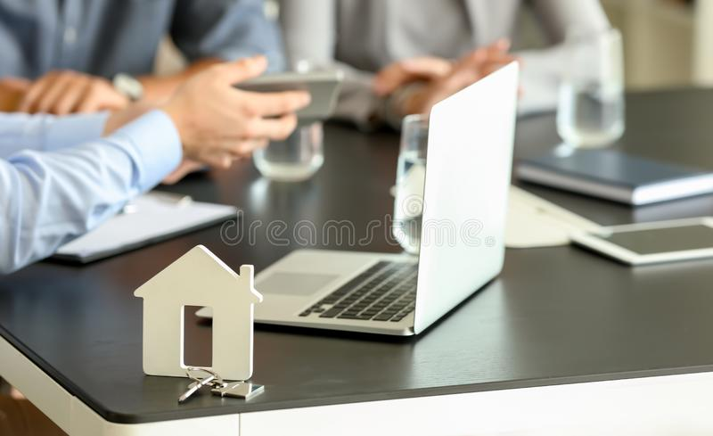 Key and laptop on table in real estate agent\'s office. Concept of buying of new house royalty free stock photography