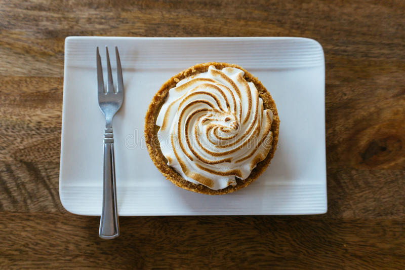 Key Lime Pie. On a white plate on wooden floor royalty free stock photography