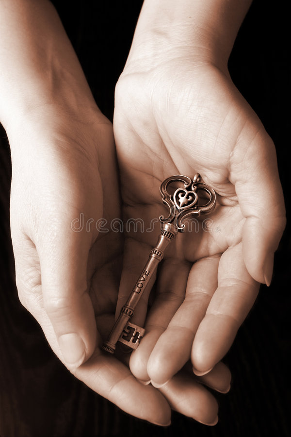 The Key of Love. Palms holding a key with engraved word Love on it royalty free stock images
