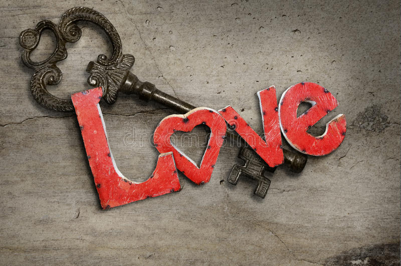 Key and Love letters. Red metal letters spelling love on top of an iron key both lying on a concrete textured surface. Concept for how to make it in love royalty free stock photos