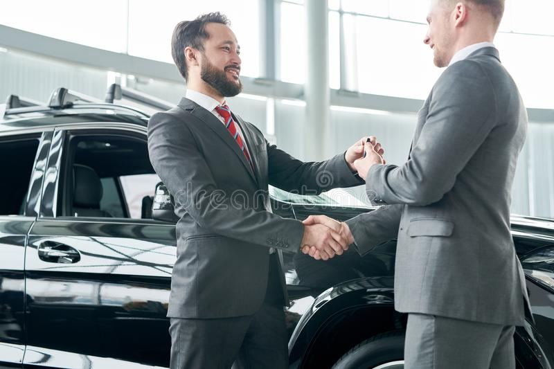 The key from new car. Salesman giving the key from new car to his client stock photography