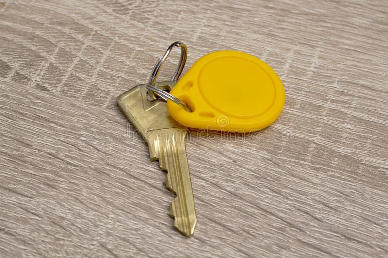 A key and a rfid tag on a key chain. On a desktop stock image