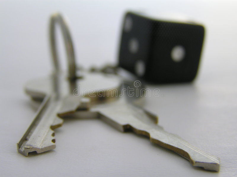 Key's and dice. Macro of keys and a dice keychain, with the focus on very front of the keys. The rest is blurred intentionally, as the keys are the main subject royalty free stock images