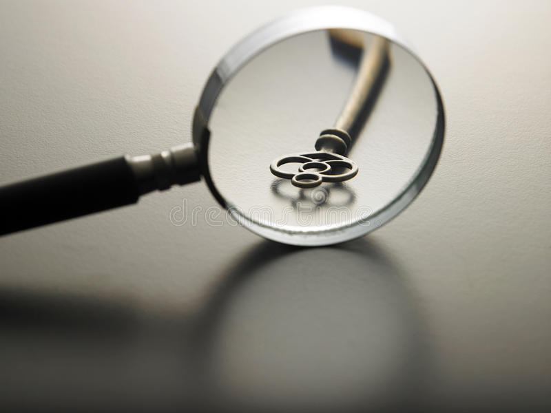 Key of success. Magnifying glass on a key stock photos