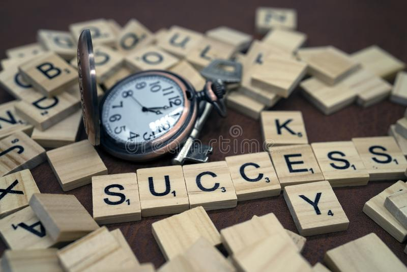 Key and success word wood box letters and small clock with metal key bussiness concept. Key and success word wood box letters and metal key and small clock with royalty free stock photos