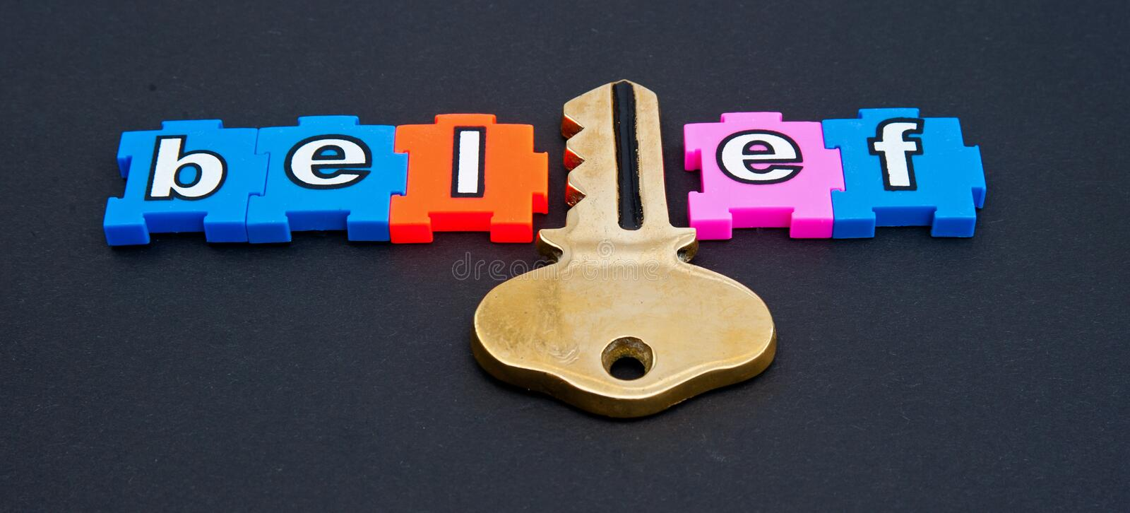 Key to belief. The word belief in colorful jigsaw type lower case letters with the 'i' replaced by a gold key isolated on dark background stock photography