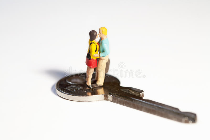 The Key To The Future. A young couple of miniature toy figures standing in a close embrace on top of a key stock photography