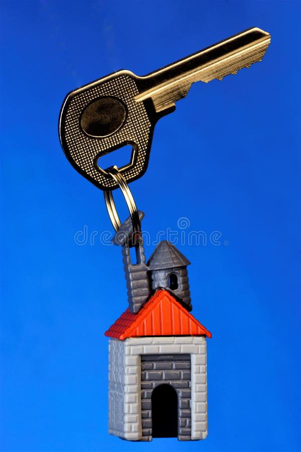 The key to the house on the keychain in the form of a house on a blue background, the territory of your comfortable property. Key royalty free stock photos
