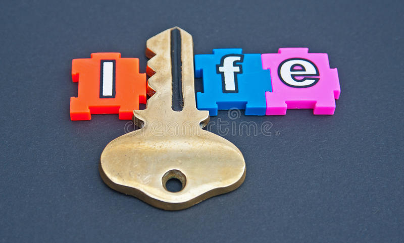 Key to life. With life spelled out in colorful jigsaw type letters with the letter 'i' replaced by a gold key isolated on a dark background royalty free stock images