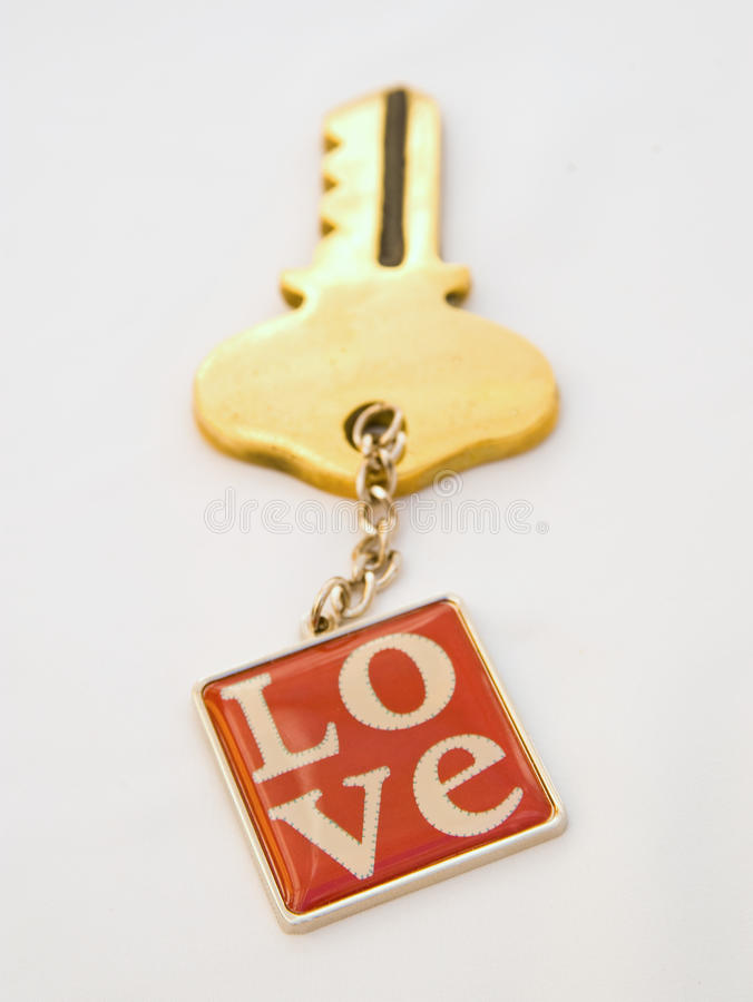 Key to love. A key ring overprinted with love and connected by a chain to a large golden key. The image is isolated against a plain bright background royalty free stock photos