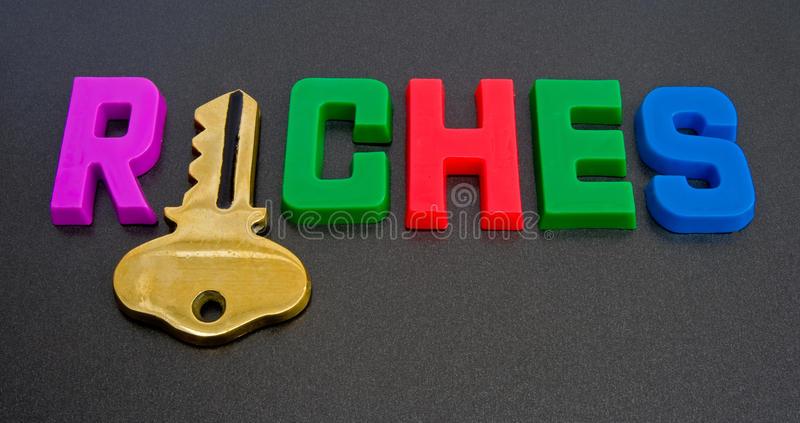 Key to riches ?. A macro image of the word riches in colorful upper case letters but with the i replaced by a gold key royalty free stock photos