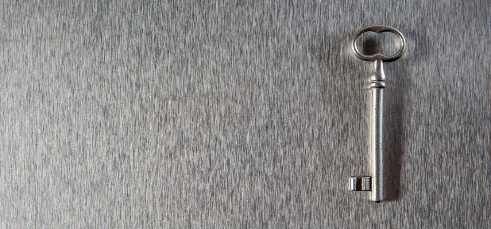 Key to safe business solution or property access, copy space. One old key on empty stainless steel background for symbol of safe business solution, investing in royalty free stock images