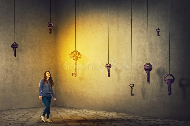 Key to success. Confident young woman walking in a dark room to find the magic key to success. Concept of business aspirations, achievement and the right choice royalty free stock photography
