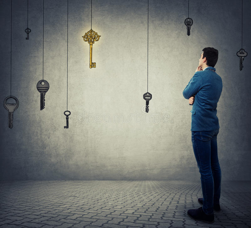 Key to success. Rear view of a young businessman thoughtful looking at a glowing golden key to success among others made of steel hanging. Concept of business royalty free stock images