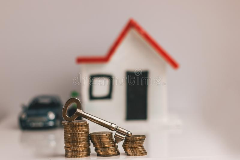 Key on top of a stack of coins with a blurred house and car on the background: real estate, property, mortgage, concept stock photography