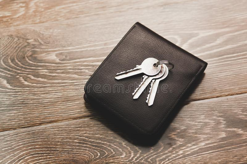 Key on wallet. On wooden table stock images