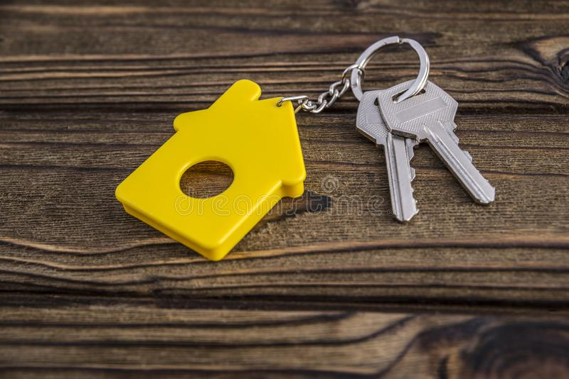 Key with yellow shaped house keychain on chain on wood texture background. stock images