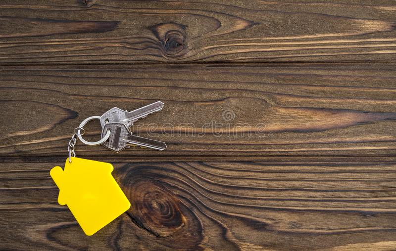 Key with yellow shaped house keychain on chain on wood texture background. stock photo