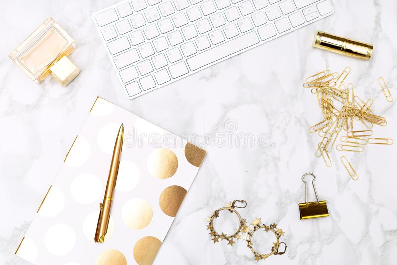 Keyboard c of office items of gold color and cosmetics on the de. Sktop of the house royalty free stock photography